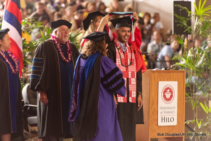 Graduate student smiles while hood is placed over his head.
