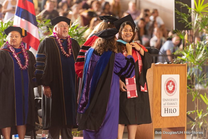 Graduate student looks to professor. smiling, as another professor places hood over her head.