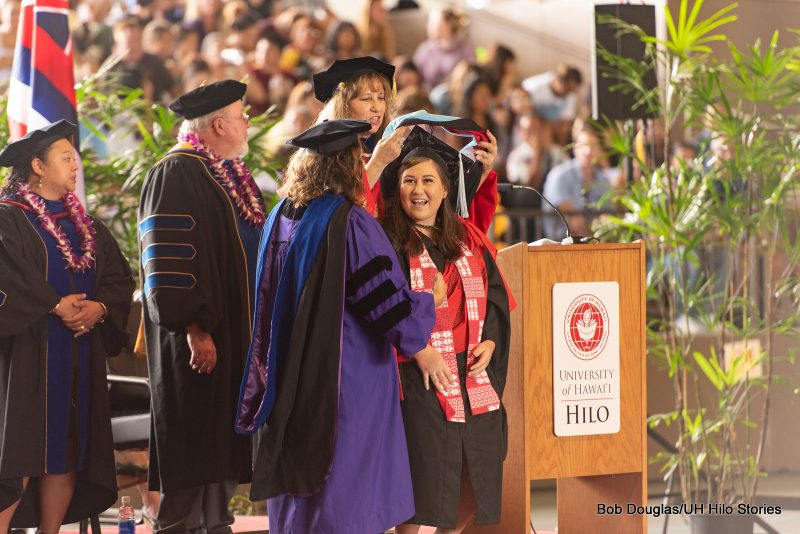 Graduate student big smile as professor places hood on her shoulders.