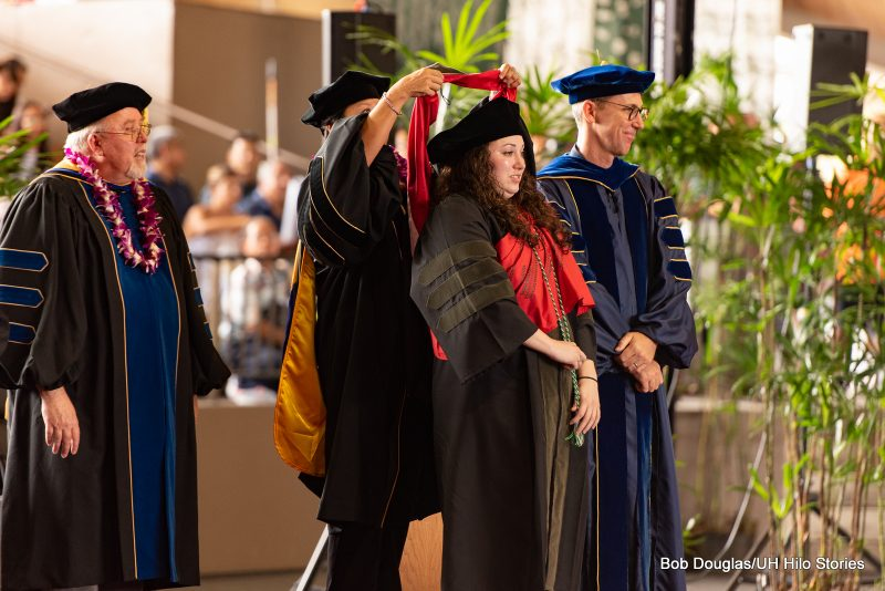 Doctoral graduate student receives hood.