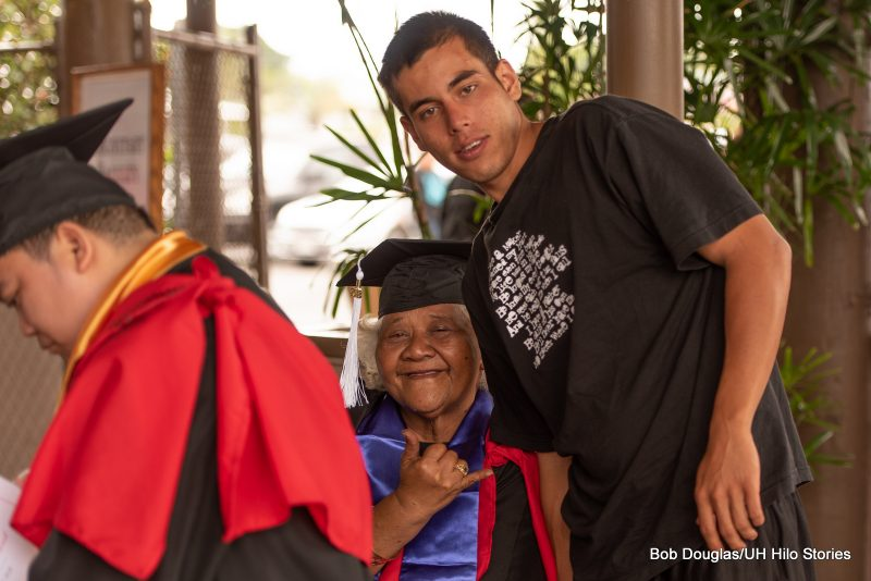 Elderly graduate with young man.