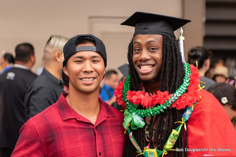 A graduate stands with his friend.