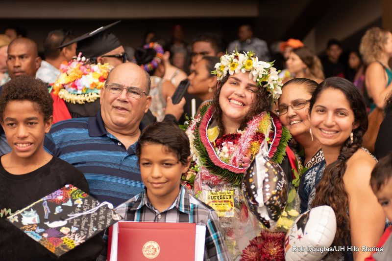 Graduate poses for photo with family.