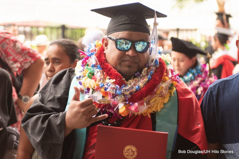 Graduate in sunglasses gives the shaka to the camera.