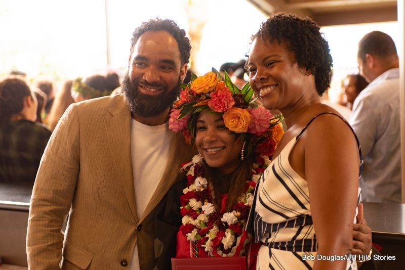 Graduate with bright golden head lei poses with family.