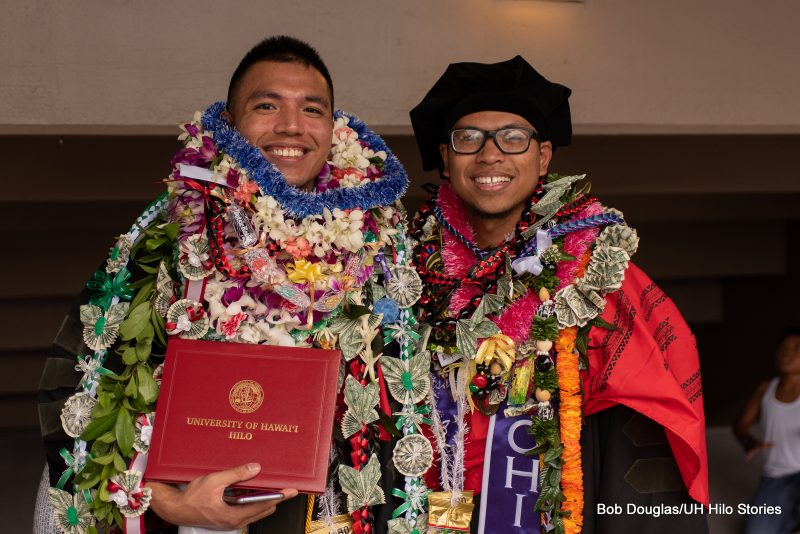 Two graduates with lei and diplomas.