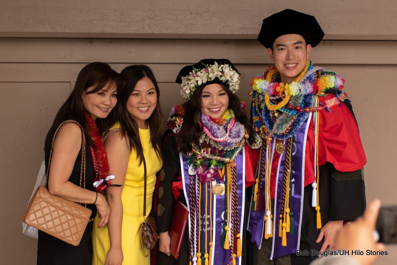 Honors graduates with sashes, lei, standing with friends.