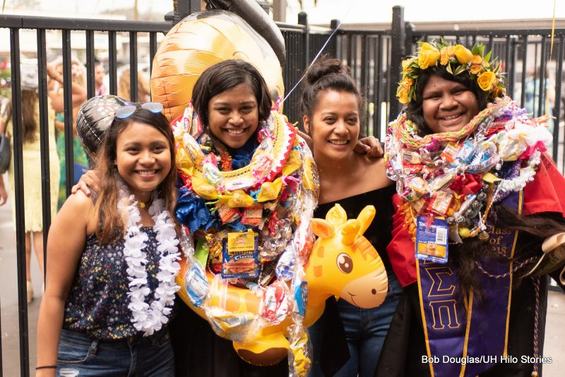 Graduate with lei and inflatable animal. life preserver
