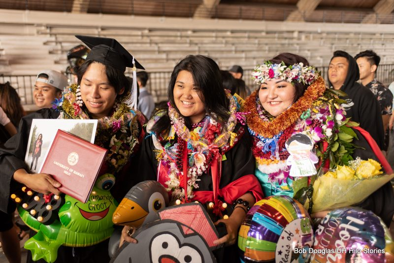 Three graduates with lei and balloons.