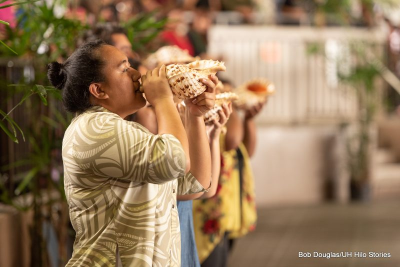 Group blows conch shells at start of procession.