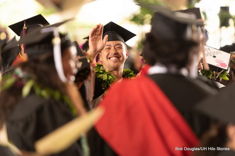 Graduate waves to crowd.