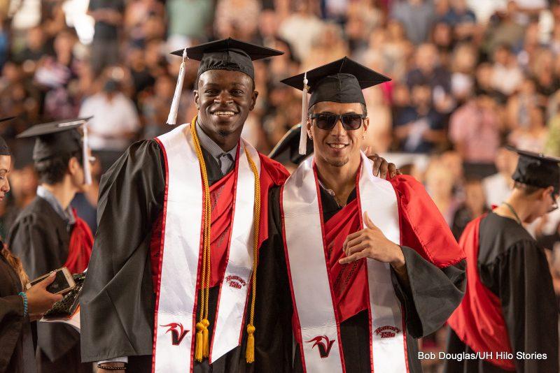 Two graduates pose for photo.