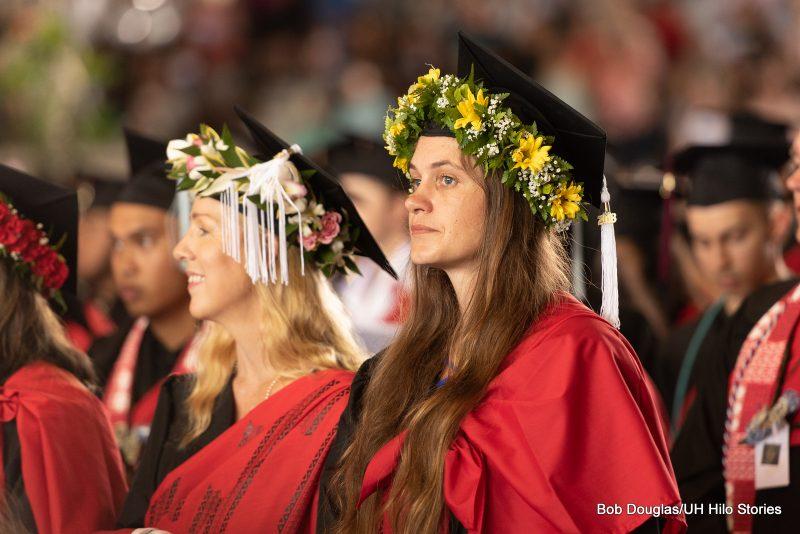 Graduates standing at seats.
