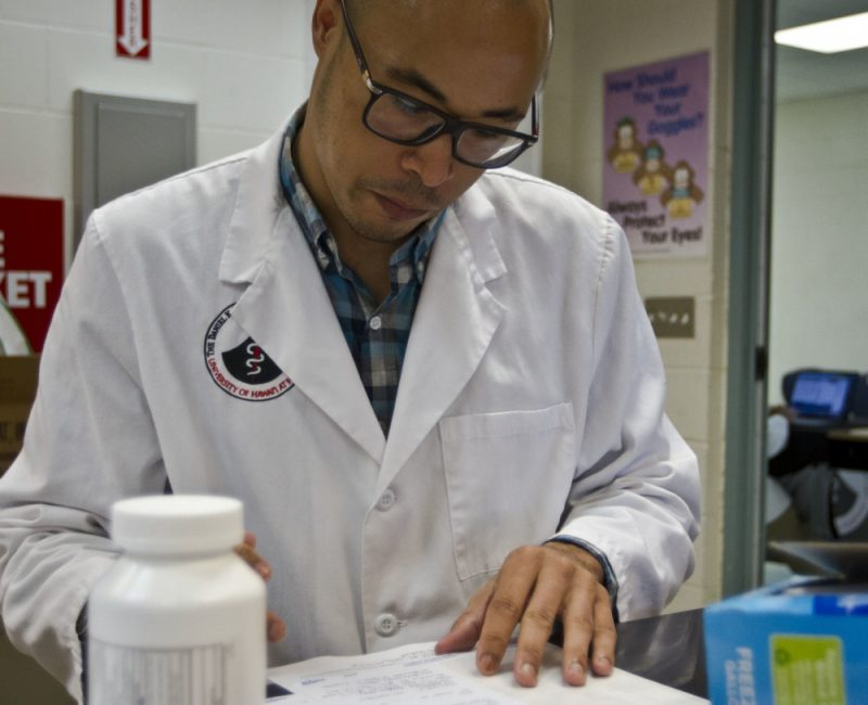 Aron Brown in while lab coat, reading paper on desk. Pill bottle in foreground.