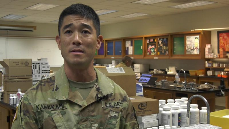 Chad Kawakami in army fatigues, in lab with boxes and bottles of medication.