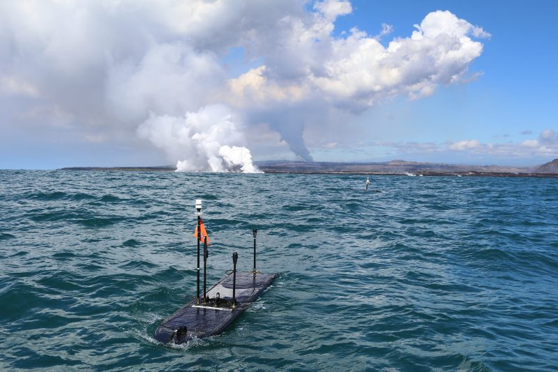 Wave gliders floating on surface of ocean, active lava flow in background with rising vog.