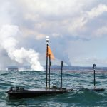 Wave glider platforms floating on ocean., plume in background.