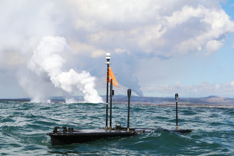 Wave glider platforms floating on ocean., plume from active lava flow in background.