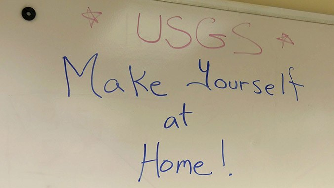 Handwritten sign with words: USGS Make Yourself at Home!