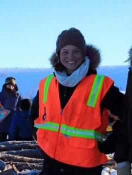 Katherine Mulliken in bright orange safety vest and wool cap.