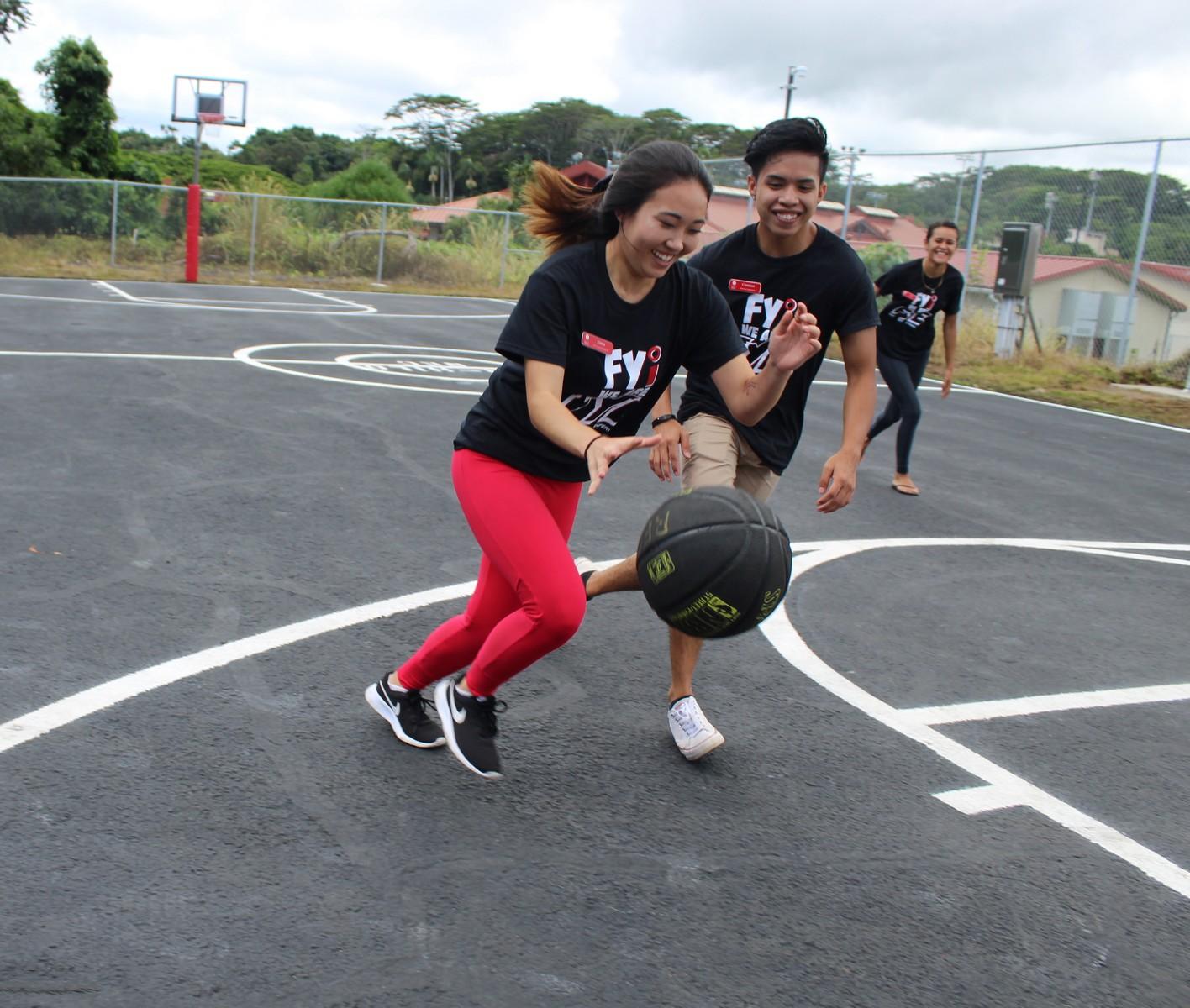 Two student playing basketball.