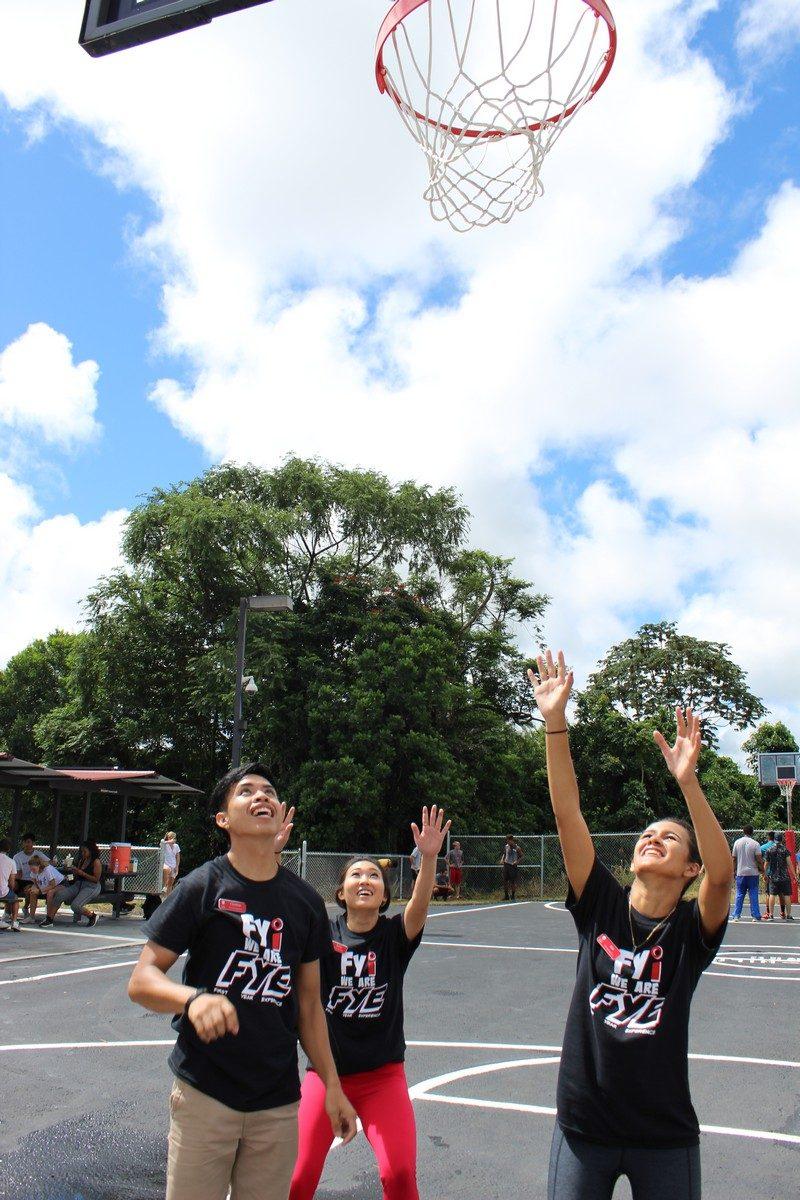 Three students shooting hoops.