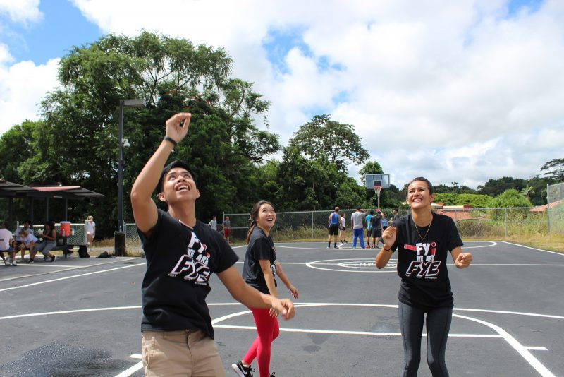 Students look up at a ball in play near the hoop.