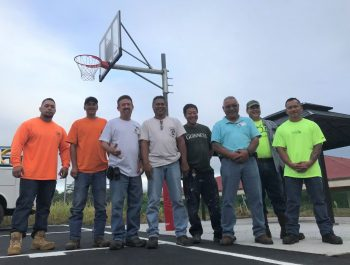 Group of men in work clothes on the basketball court pose for photo.