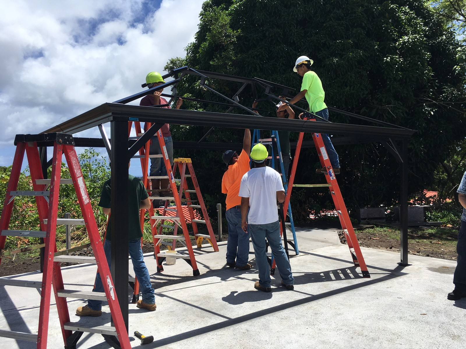 Group of workers, one on ladder, working on gazebo frame.