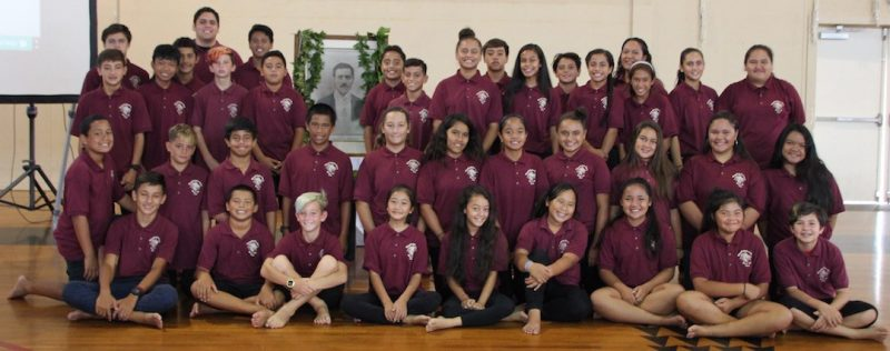 Large group of school children seated/standing for photo in matching maroon shirts.