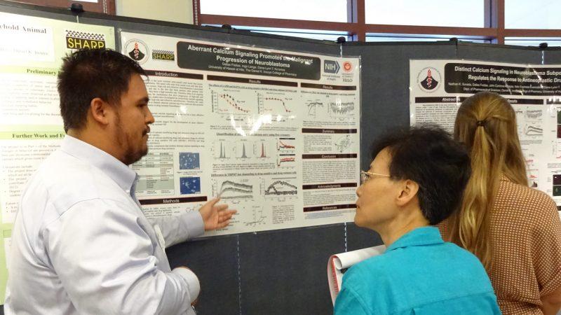Dallas Freitas points to his poster while explaining to visitor.