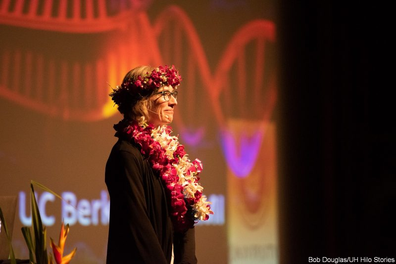 Jennifer Doudna, in lei and haku head lei. speaks at the podium.