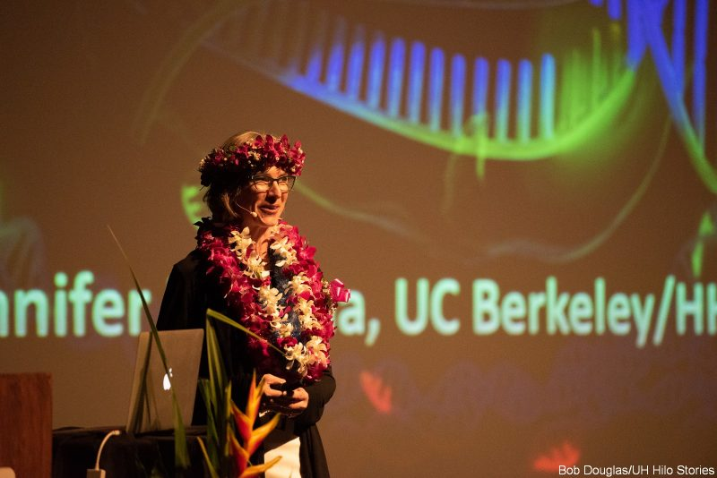 "Jennifer Doudna speaks at the podium. Her name and ""UC Berkeley"" is on the large screen behind her."