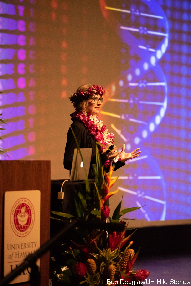 Jennifer Doudna at the podium, with lei. In the background is a DNA strand up on a large screen.