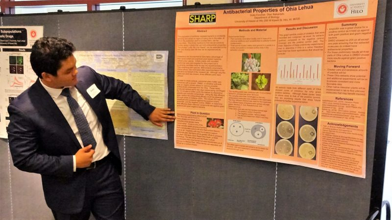 Duke Escobar pointing to his poster presentation. The words on the poster cannot be made out, but at the top is the title: Antibacterial Properties of Ohia Lehua, and the acronym SHARP in the top left corner. Duke is wearing a suit and tie.