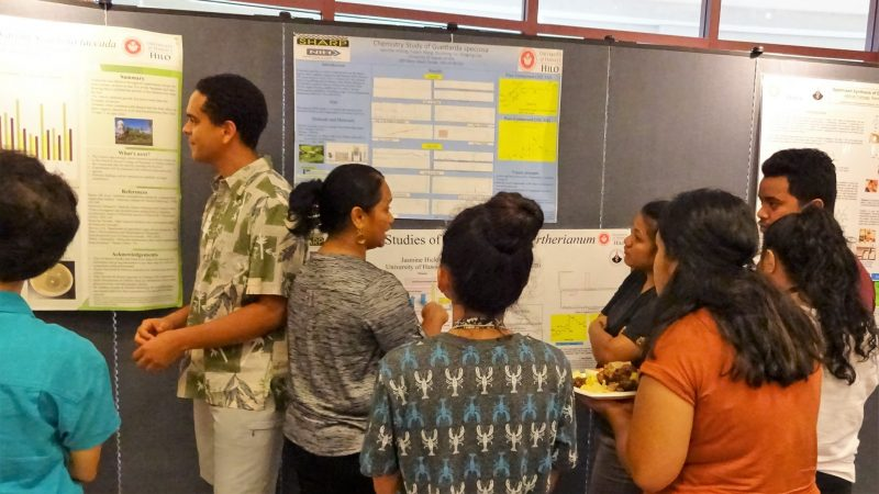 Jasmine Hiking and a group of people at her poster presentation.