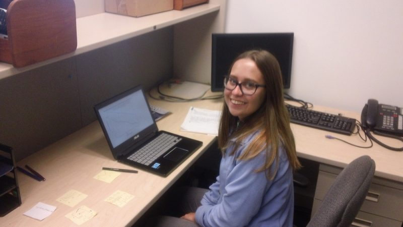 Channtelle Kiessner sits at a cubicle desk with an open laptop in front of her.