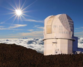 Daniel K. Inouye Solar Telescope, a round, tall white structure above the clouds. In the sky is a dazzling sun with extended rays.