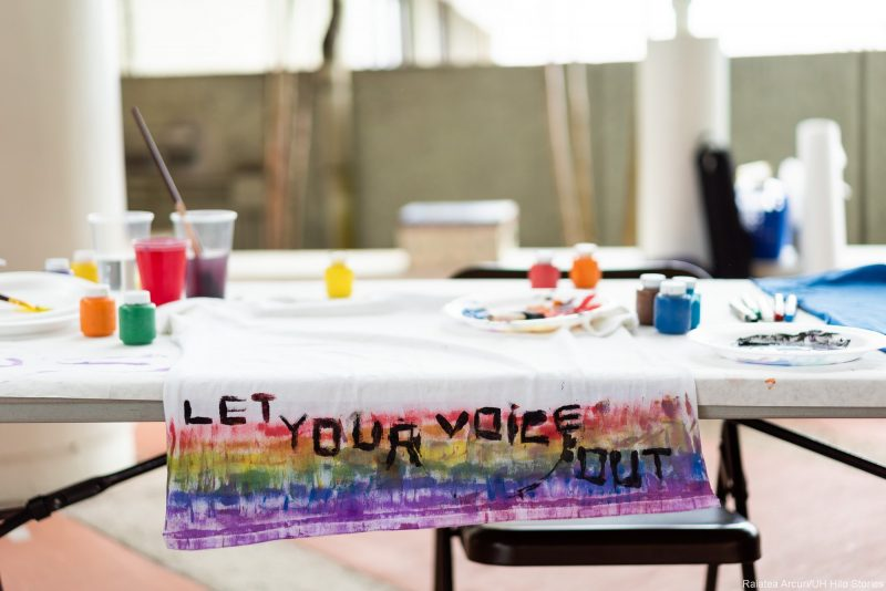 Table with paint supplies like pots of paint, brushes, plates to mix colors. Words painted on a sign: LET YOUR VOICE OUT.