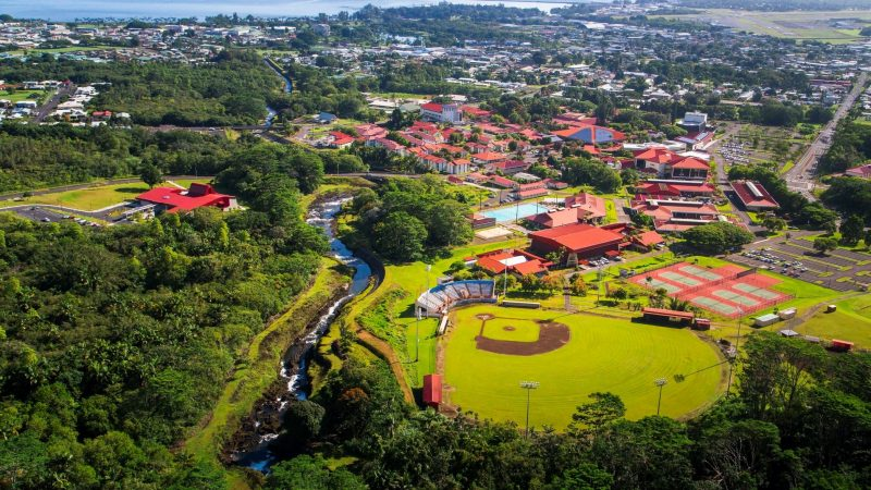 Aerial of campus showing red roofs, baseball field, pool, tennis courts, with Hilo Bay in far background.