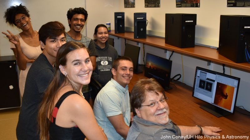 Group of students and the professor, near the bank of new computers, turn to smile at camera. Watermark: Photo by John Comey/UH Hilo Physics and Astronomy.