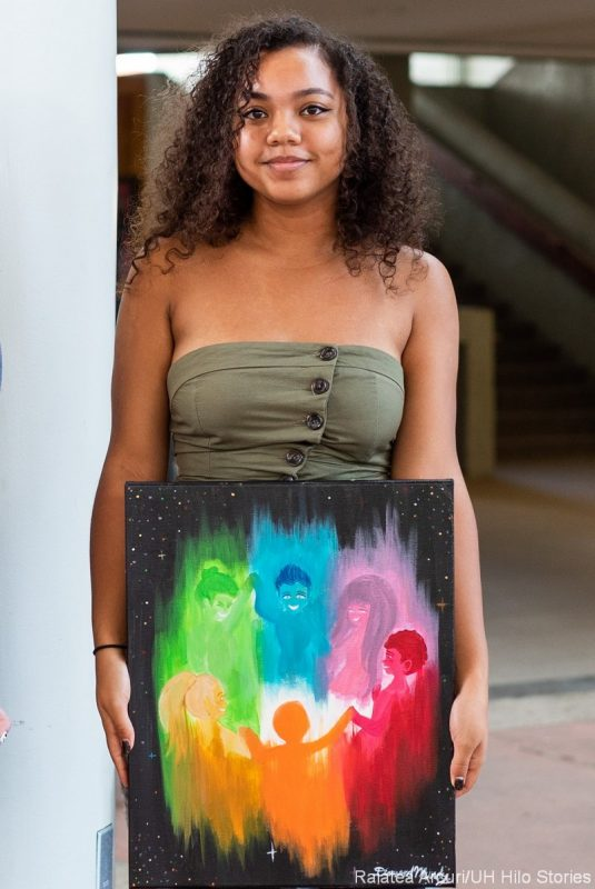 Diamond Mundy holds her artwork, human figures in a circle, all in rainbow colors against a black background.