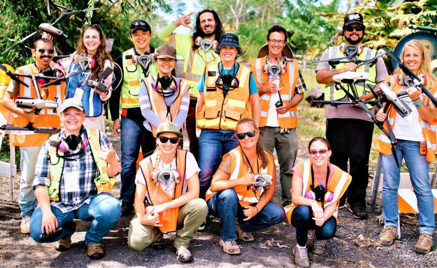 Group photo of the drone team, 13 people, all wearing reflective jackets. All have gas masks around their necks. Some are holding drones and/or drone equipment. The photo is taken on a dirt road with access blocked off.