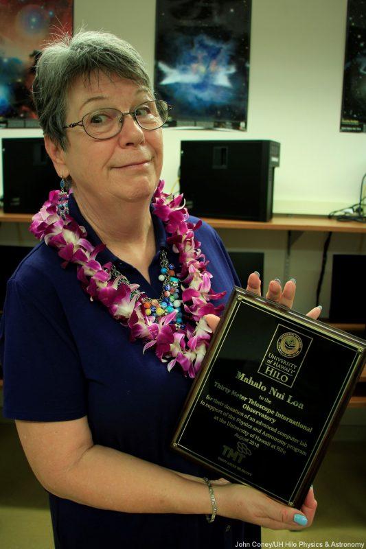 Sandra Dawson holds plaque. On plaque, the words: Mahalo Nui Loa.