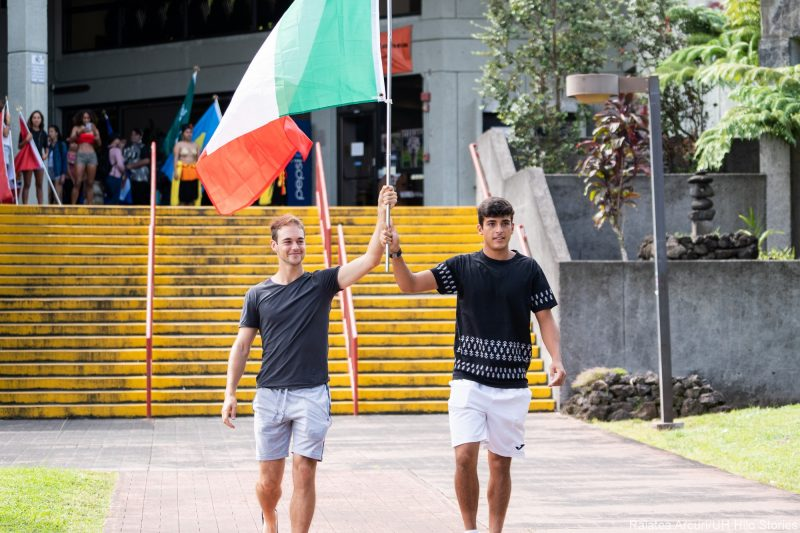 Two male student both hold staff for green, white and red flag of Italy.