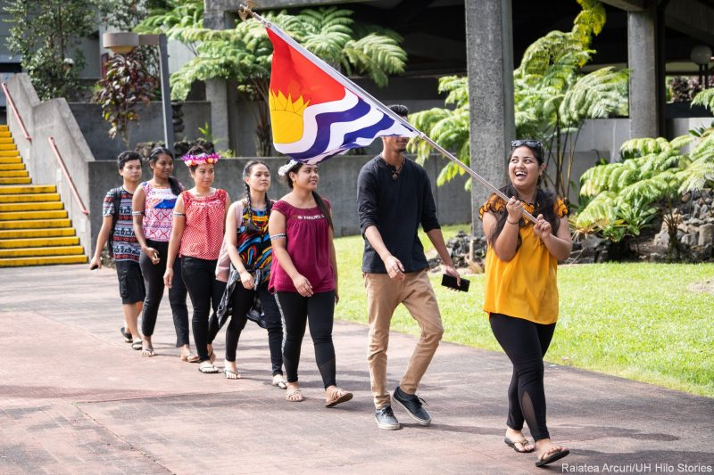 Large group of students walk into venue in a line, the first person, a young woman, carries red, yellow, blue and white flag of Kitibati. The blue looks like water.