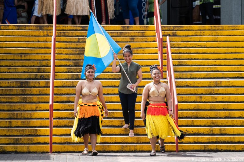 Two students in traditional attire and one woman in modern pants (with blue and white flag of Palau), walk down stairs.