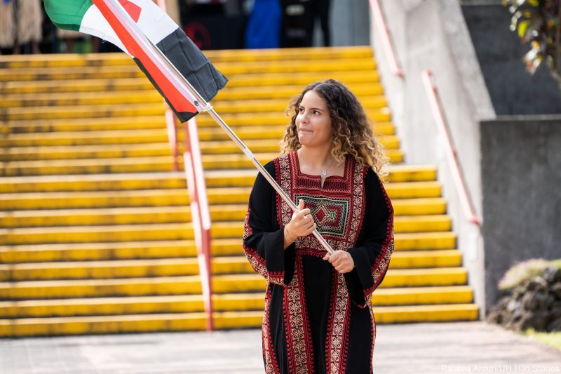 A young woman carries black, white and red flag of Jordan