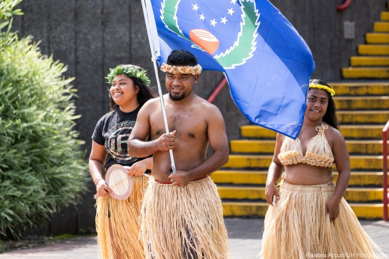 Young man and two young women in grass skirts enter the venue. The male carries the blue and green flag of Pohnpei.
