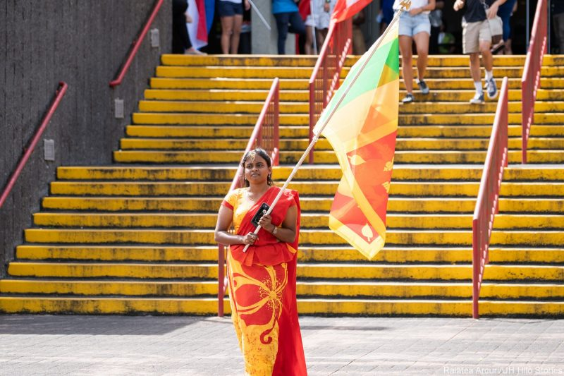 Young woman enters venue carrying green, yellow and red flag of Sri Lanka.